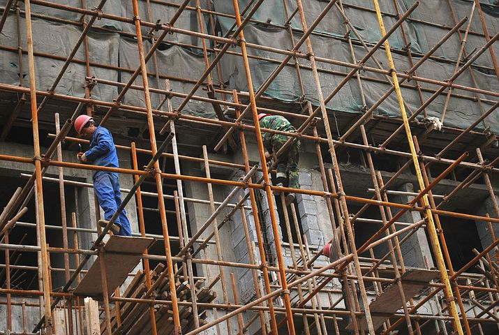 Two men working while on scaffolding.